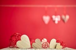 Herzen auf Holztisch- und Rothintergrund Stockbild