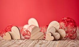 Herzen auf Holztisch- und Rothintergrund Stockfoto