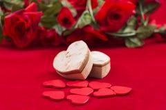 Herzen auf Rot mit Rosen im Hintergrund Lizenzfreie Stockfotos