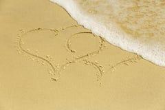 Herzen der Aufschrift zwei auf dem Strand in der Gischt Stockfotografie