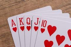 Herzen entsprechen Spielkarten auf hölzernem stockfoto