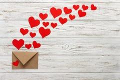 Herzen fliegen heraus vom Umschlag Umschlag mit Innerem Hintergrund Valentine Day auf hölzernem Hintergrund Stockfotos