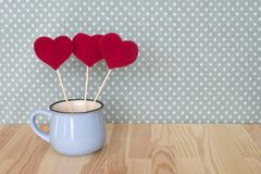 Herzen im blauen Becher für Valentinsgruß-Tag auf hölzernem Hintergrund Stockfotografie