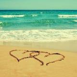 Herzen im Sand eines Strandes Stockbilder