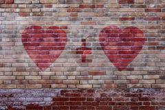 Herzen mit Pluszeichen auf gealterter Backsteinmauer Stockbilder