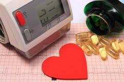 Herzform, Blutdruckmonitor und Tabletten auf Elektrokardiogramm Lizenzfreies Stockbild