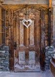 Herzform deco auf Holztür Stockfotografie