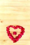 Herzform gemacht aus rosafarbenen Blumenblättern heraus auf hölzernem Hintergrund, Valentin vektor abbildung