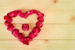 Herzform gemacht aus rosafarbenen Blumenblättern heraus auf hölzernem Hintergrund, Valentin stock abbildung