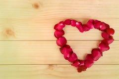 Herzform gemacht aus rosafarbenen Blumenblättern heraus auf hölzernem Hintergrund, Valentin lizenzfreie abbildung
