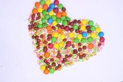 Herzform gemacht mit Bohnen und Süßigkeiten lizenzfreie stockfotos