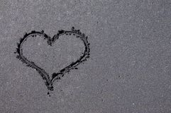 Herzform gezeichnet auf schwarzen Sandstrand stockfotografie