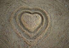 Herzform im Sand auf dem Strand, Draufsicht Stockbilder