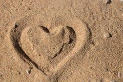 Herzform im Sand stockbilder