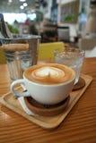 Herzform Latte-Kunstkaffee auf der Bauholztabelle in der Kaffeestube Stockbild