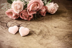 Herzform mit Rosarosenblume auf Holztisch Stockfotos