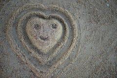 Herzform mit smiley im Sand auf dem Strand Beschneidungspfad eingeschlossen Stockbilder