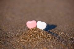 Herzform mit zwei Sanden im Sand durch das Meer Stockbilder