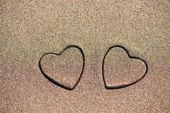 Herzform mit zwei Sanden im Sand durch das Meer Lizenzfreie Stockfotos