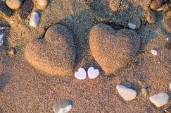 Herzform mit zwei Sanden im Sand durch das Meer Lizenzfreies Stockbild