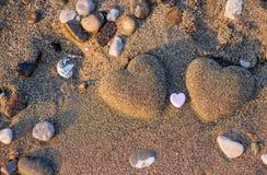 Herzform mit zwei Sanden im Sand durch das Meer Stockfotos