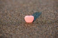 Herzform mit zwei Sanden im Sand durch das Meer Lizenzfreie Stockbilder
