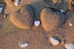 Herzform mit zwei Sanden im Sand durch das Meer Stockfoto