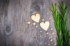 Herzform und grünes Laub auf hölzernem Beschaffenheitshintergrund, lizenzfreie stockbilder