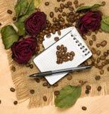Herzform von den Kaffeesamen auf Leerbeleg und roten Rosen Stockfotografie