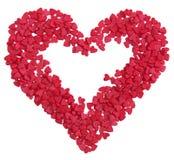 Herzform von der Herzsüßigkeit besprüht über Weiß Lizenzfreie Stockfotografie