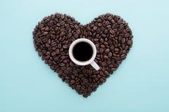Herzform von Kaffeebohnen u. Tasse Kaffee auf Blau Lizenzfreie Stockfotos