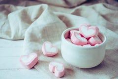 Herzformeibische im weißen Becher auf dem hölzernen Hintergrund, süß Stockbild