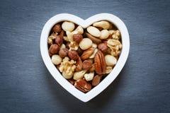 Herzformschüssel füllte mit gemischten rohen Nüssen stockfoto