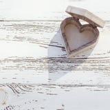 Herzholzkiste auf weißem Holz Stockfotografie
