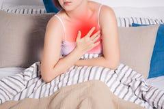 Herzinfarkt, Frau mit dem Schmerz in der Brust, der zu Hause leidet lizenzfreie stockfotografie