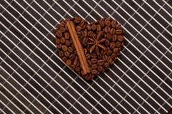 Herzkaffeerahmen gemacht von den Kaffeebohnen auf hölzerner Beschaffenheit, Zimt Lizenzfreie Stockfotografie