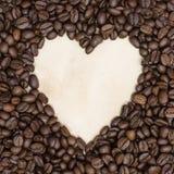 Herzkaffeerahmen gemacht von den Kaffeebohnen auf Weinlesepapier Stockfotografie