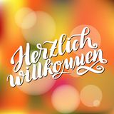 Herzlich willkommen. Welcome. Traditional German Oktoberfest bier festival . Vector hand-drawn brush lettering illustration on ora. Nge blurred background Royalty Free Stock Photos