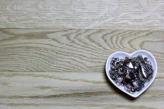 Herzperlen des Metalls auf hölzernem Hintergrund Lizenzfreie Stockfotos