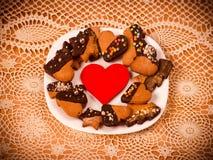 Herzplätzchen auf einem hölzernen braunen Hintergrund, Nudelholz Konzept von Feiertags-Valentinsgruß ` s Tag oder Weihnachten und Stockfoto