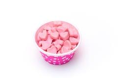 Herzsüßigkeit in den Papierschalen des rosa Tupfens lokalisiert lizenzfreie stockbilder