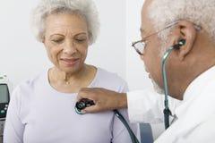 Herzschlag Doktor-Checking Patients unter Verwendung des Stethoskops Stockbilder