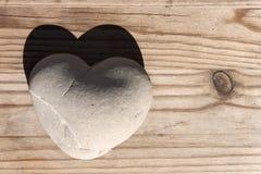 Herzstein mit Schatten auf Holztisch Stockfotografie