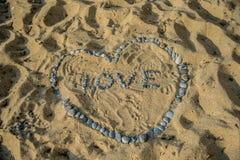 Herzsymbol und Wortliebe auf Sand Stockfoto