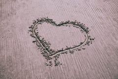 Herzzeichen eigenhändig gezeichnet auf sandigen Strand Lizenzfreies Stockfoto