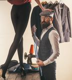 Hes一位主要裁缝 有胡子的人女装裁制业女性衣裳在裁缝商店 专业裁缝或时尚编辑在 免版税库存照片