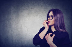 Hesitant anxious woman biting her fingernails looking sideway. Side profile hesitant anxious woman biting her fingernails looking sideway isolated on gray wall Royalty Free Stock Photos