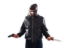 Hesitant assassin choosing his weapon. Hesitant assassin dressed as a pilot is choosing his weapon for the next crime holding a gun and a knife in his hands Stock Photos