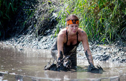 Hesitant athlete in the mud. A woman appears to be a bit hesitant to wade into the muddy river course at the 2014 Indiana mudathlon Stock Images