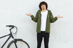 Hesitant curly man shruggs shoulders in bewilderment, dressed in fashionable green anorak, stands near bicycle, isolated over. White background, doesnt know stock image